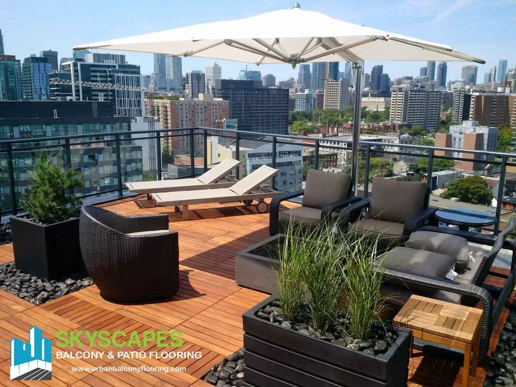 Rooftop patio lined with Ipe structural wood tiles. Skyscapes green and blue logo at bottom-left of image.