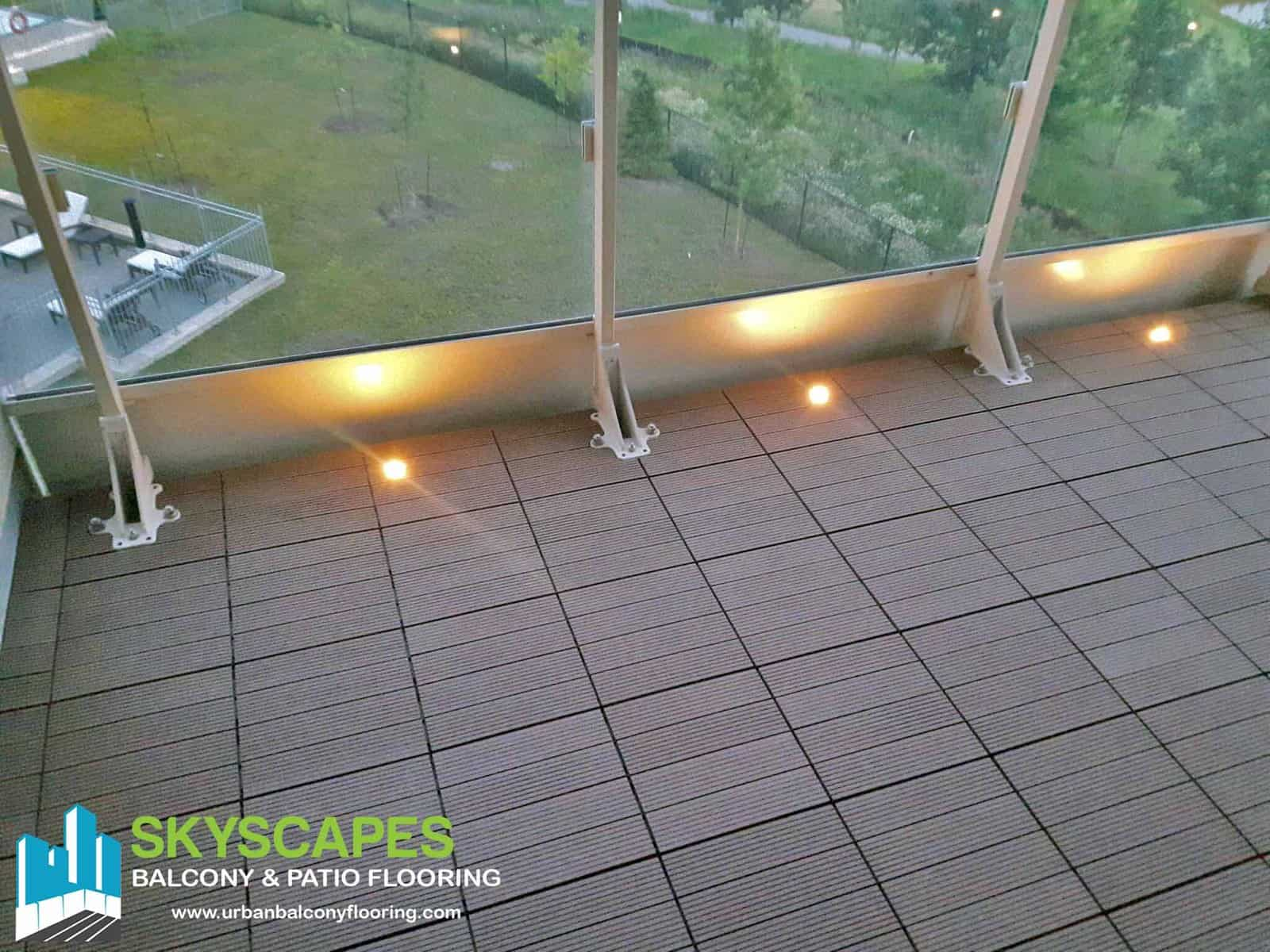 Teak Composite Tiles and Lights on Toronto Balcony. Ridged WPC Tile seen on balcony floor. Measures 1 by 1 feet. Skyscapes green and blue logo at bottom-left of image.