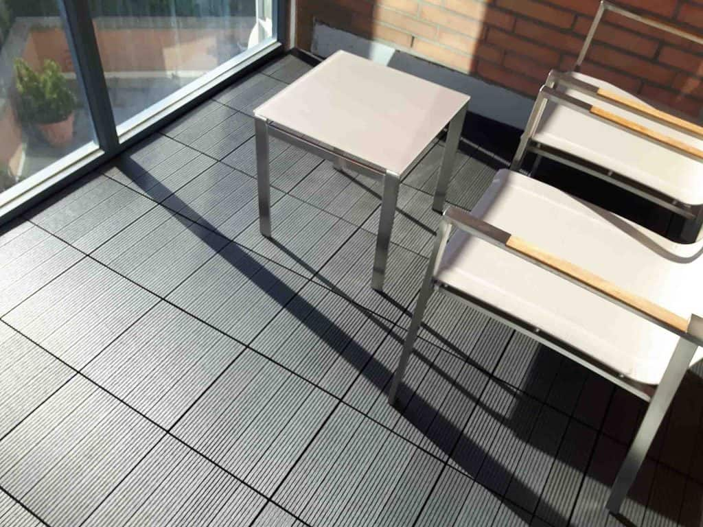 Charcoal, 4-slat, ridged WPC Tile seen on balcony floor with nice modern furniture. Measures 1 by 1 feet.