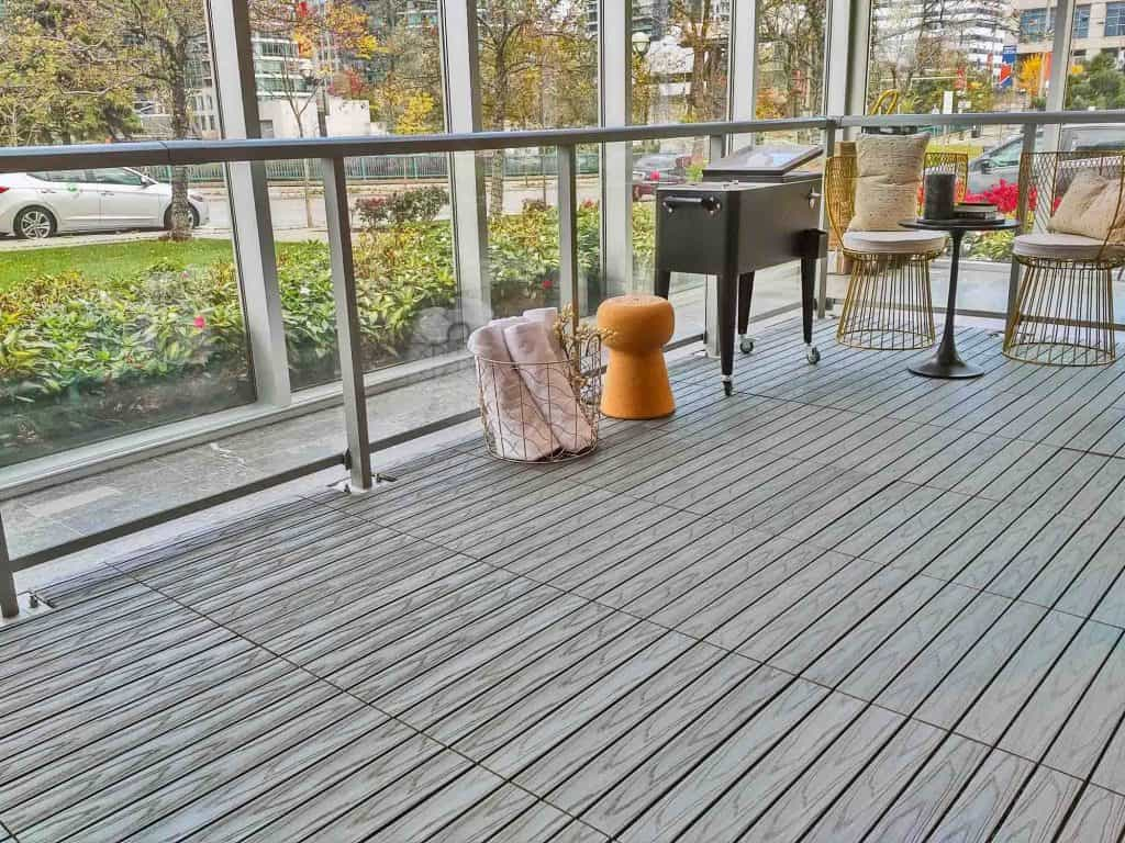 Grey oak, 4-slat, embossed WPC Tile seen on angle on indoor terrace. Each tile measures 2 by 1 feet.