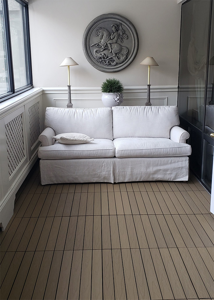 white couch in outdoor room with composite flooring