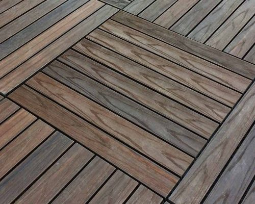 Closeup of walnut composite deck tiles arranged in large squares in parquet pattern